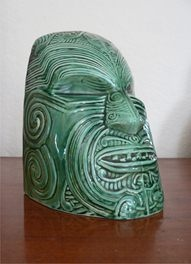 Wharetana Maori Art Pottery 'Moko' Bookend. A ceramic representation of ceremonial life-sized wooden masks which were hollowed out to allow fitting over a head. Glossy deep jade glazed, shape number 1019 base impressed.