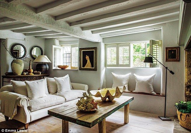 In the living room, shades of white and grey are layered with weathered wood in varying tones and textures. The sofas are by Flamant (flamant.com) and the linen cushions are by Linum (linumdesign.com)