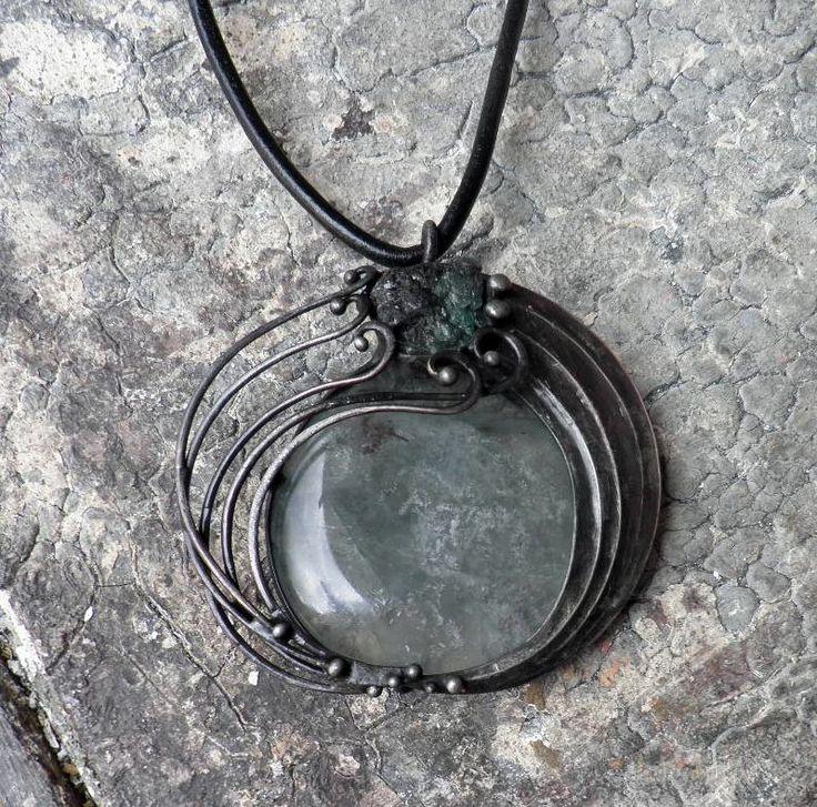 Meandr smaragdové řeky... Šperk je vyroben z cínu, který byl patinován a ošetřen antioxidačním olejem... Vsazeným minerálem je fluorit a smaragd v mateční hornině. Rozměry šperku jsou cca 6 x 6,5 cm. Šperk je zavěšen na kožený řemínek délky cca 45 cm, který je zakončen naším originálním, ručně vyrobeným zavíráním. Jeden konec řemínku do koncovky nevlepujeme, ...