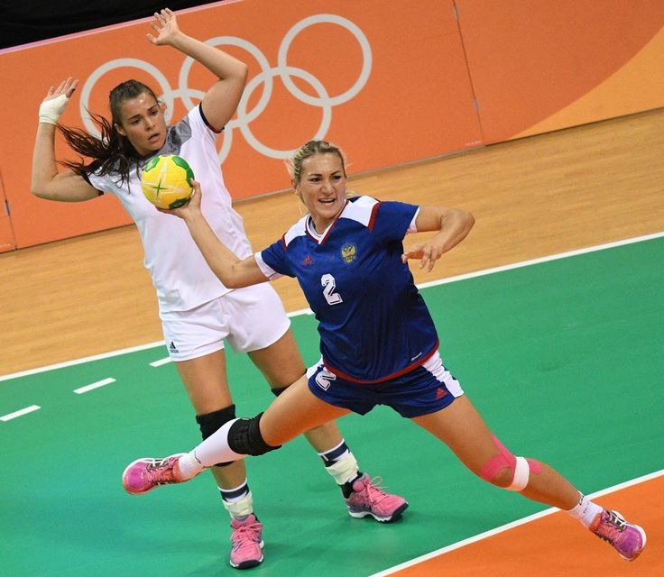 Russia's left wing Polina Kuznetsova (front) shoots past France's right wing Marie Prouvensier during the women's Gold Medal handball match France vs Russia for the Rio 2016 Olympics Games at the Future Arena in Rio on August 20, 2016. / AFP / afp / Roberto SCHMIDT