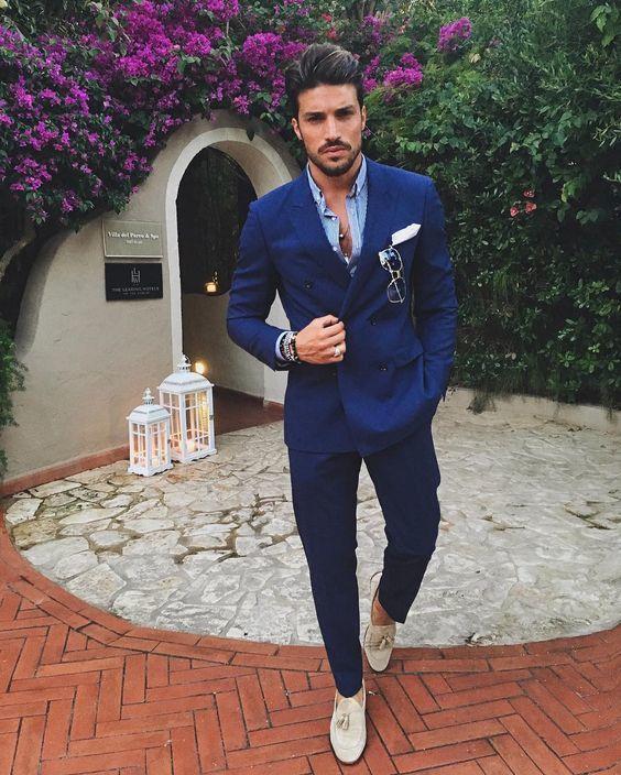 Acheter la tenue sur Lookastic: https://lookastic.fr/mode-homme/tenues/costume-bleu-marine-chemise-a-manches-longues-bleue-claire-mocassins-a-pampilles-beiges/20937 — Chemise à manches longues bleue claire — Pochette de costume blanc — Costume bleu marine — Mocassins à pampilles en daim beiges