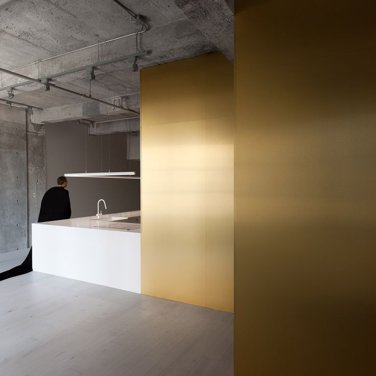 Canadian architect Jean Verville has combined minimalism with theatrics in this dwelling for a musician that features brass walls and raw concrete beams.