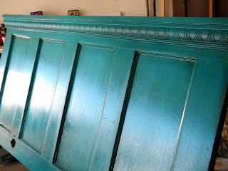 Old door as headboard... just add crown molding and paint! I want it!  Love the color and glazing.