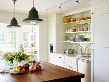 "Jim Dixon, an architect in upstate New York, included these antique dark-green enameled hanging lamps, sourced from a local dealer, Sandy Klempner, for a country-style kitchen.  ""They were originally in a Hudson Valley factory but were then restored,"" says Dixon. ""We love the look — industrial but not cold. And the pop of color is a welcome addition to the white cabinetry and the exposed beams."" The kitchen is also lit by unobtrusive white track lighting."