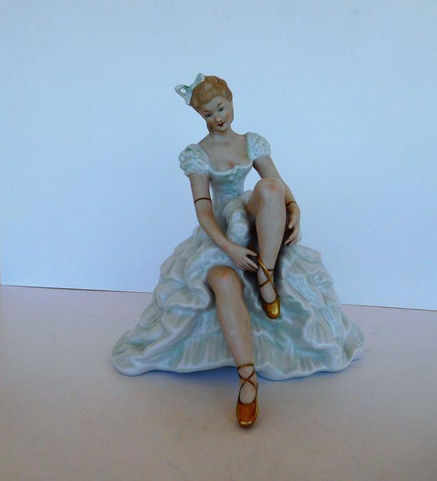 Wallendorf - een heel mooi porselein ballerina beeldje.  Een zeer mooie porseleinen beeldje van Wallendorf - Duitsland - tweede helft van de 20e eeuw. Verzegeld in de base.Deze mooie porseleinen ballerina zit op een sierlijke bankje haar slipper aan te passen. Haar jurk is lagen van uitbundige ruches. Ze is het dragen van gouden slippers en haar arm is versierd met gouden armbanden.  Haar gezicht is sereen en mooi. Het beeldje heeft elegante beweging en zeer mooie details.Zeer goede staat…