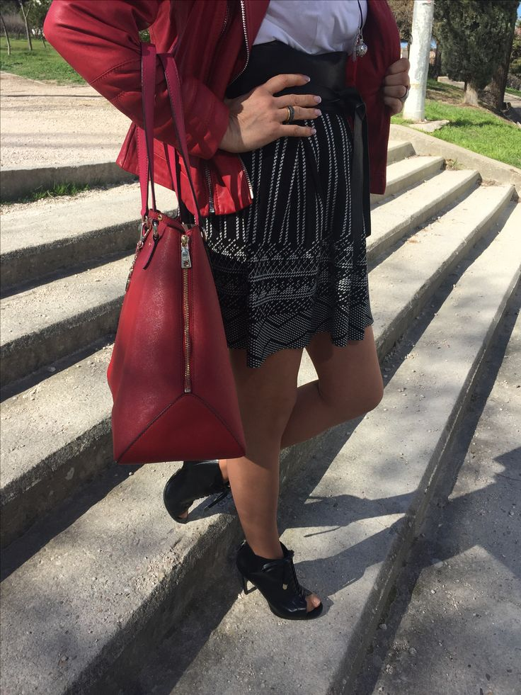 Falsa blanca y negra, cazadora perfecto roja, botines negros de tacón, bolso rojo.