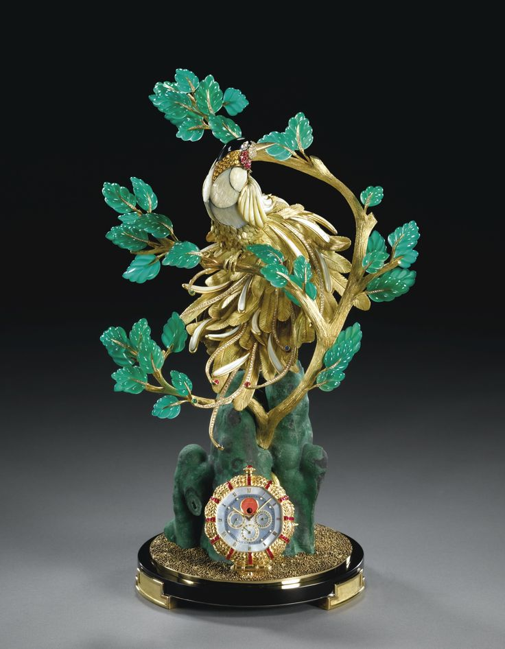 "GERALD GENTA BIRD OF PARADISE CLOCK A SPECTACULAR YELLOW GOLD, DIAMOND, RUBY, BLUE AND YELLOW SAPPHIRE, EMERALD, MOTHER-OF-PEARL, ONYX AND NATURAL MALACHITE PERPETUAL CALENDAR PRESENTATION CLOCK WITH PHASES OF THE MOON CIRCA 1990 ""UNIQUE PIECE"""