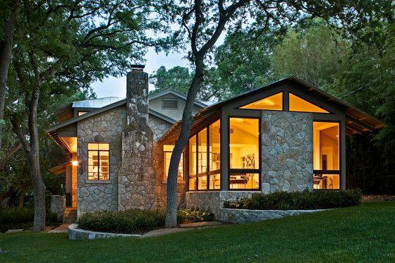 casa rustica revestida de piedra, combinada con marcos en madera y los techos a dos aguas