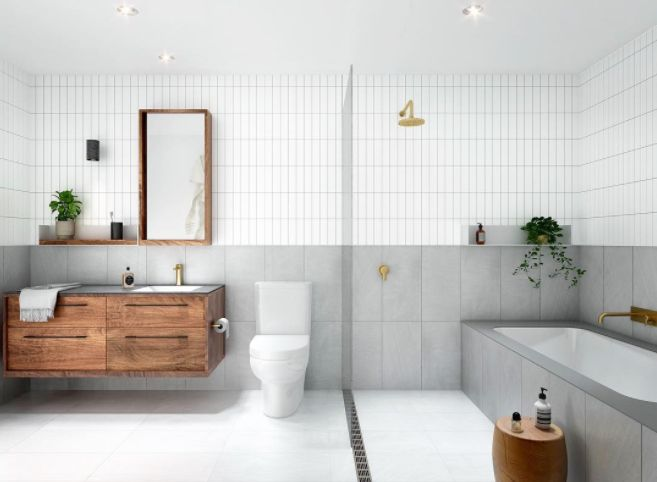 Contemporary and masculine bathroom featuring concrete look wall tiles, brass tapware and dark timber joinery. The clean lines in this bathroom are everything!
