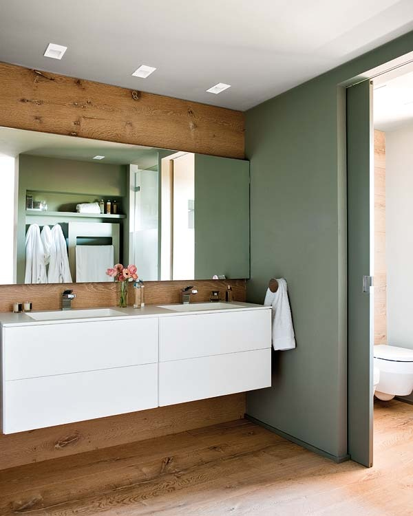double vasque, grand miroir, mur de bois et porte coulissante sur le couloir.