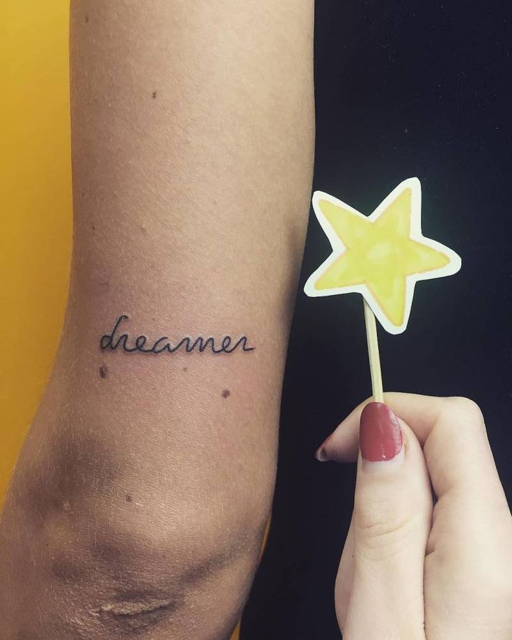 """""""Dreamer"""" tattoo on the back of the left arm."""