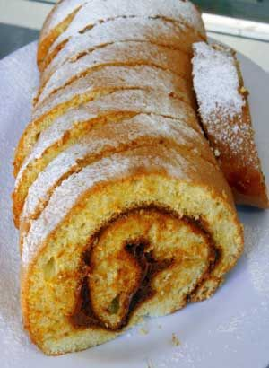 Brazo de Reina - Chilean jelly roll cake.  (A Swiss roll or jelly roll is a type of sponge cake roll. The thin cake is made of flour, eggs, and sugar and baked in a very shallow rectangular baking tray, called a sheet pan. The cake is removed from the pan and spread with jam or buttercream, rolled up, and served in circular slices.)