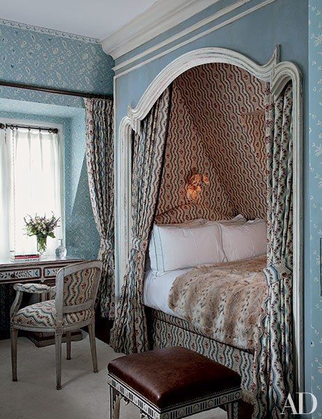 In an attic room for guests, the bed is contained in a chintz-lined niche with a rococo frame | archdigest.com