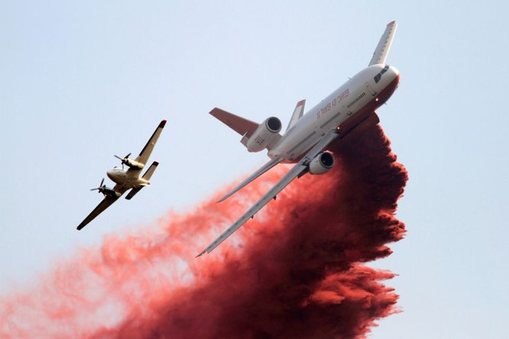 A firefighting tanker plane drops fire retardant on homes threatened by the Taylor Creek Fire outside Cle Elum, Washington.