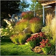 landscaping with ornamental grasses | Lake house landscape with local boulders and ornamental grass ...
