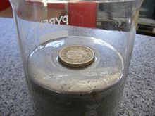 A pound coin (density ~7.6 g/cm3) floats in mercury due to the combination of the buoyant force and surface tension.
