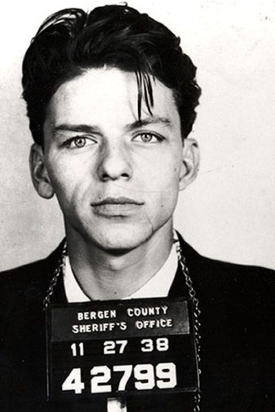 """Frank """"Blue Eyes"""" Sinatra poses for a mug shot after being arrested and charged with """"carrying on with a married woman"""" in Bergen County, New Jersey in 1938. Photo by Michael Ochs Archives"""