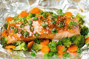 Este salmón está bien cocinado en un sobre de papel aluminio con trocitos de brócoli, zanahoria y jengibre. Todo llevado al horno para que este sude
