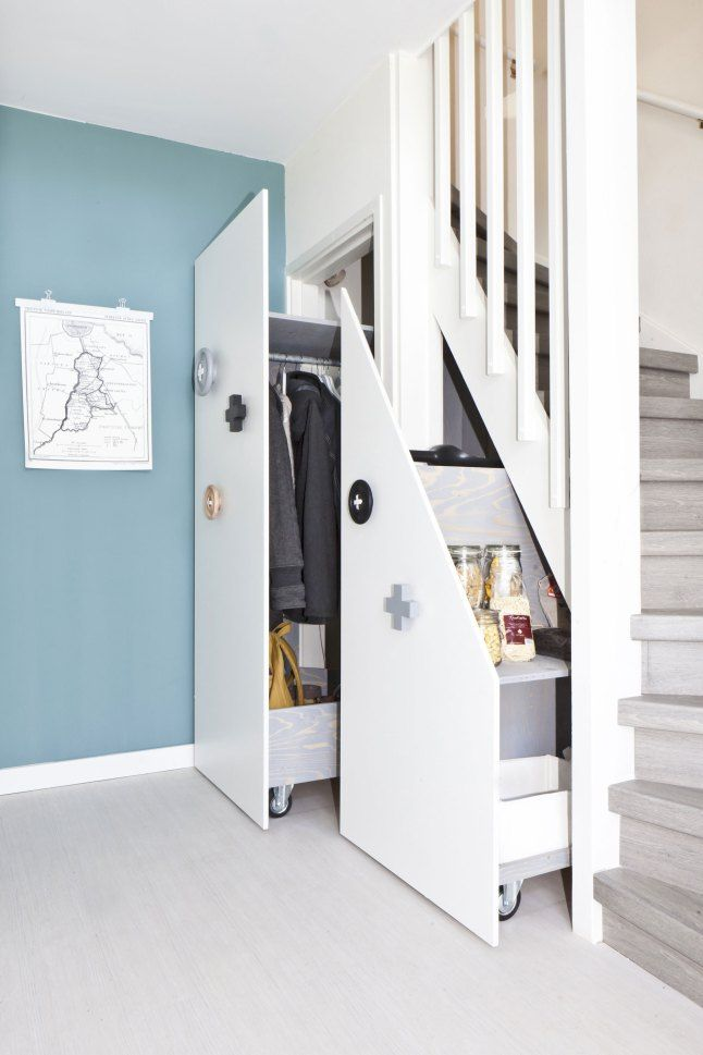 open shelf with wheels under stairs