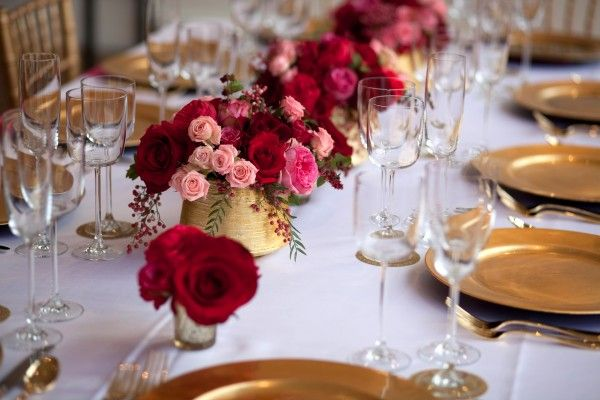 vivid color palette of metallic gold, red and pink, and accented it with some glitz and glamour with gold chargers and chivari chairs from The Party Place.  The positively gorgeous centerpieces of pink and red roses