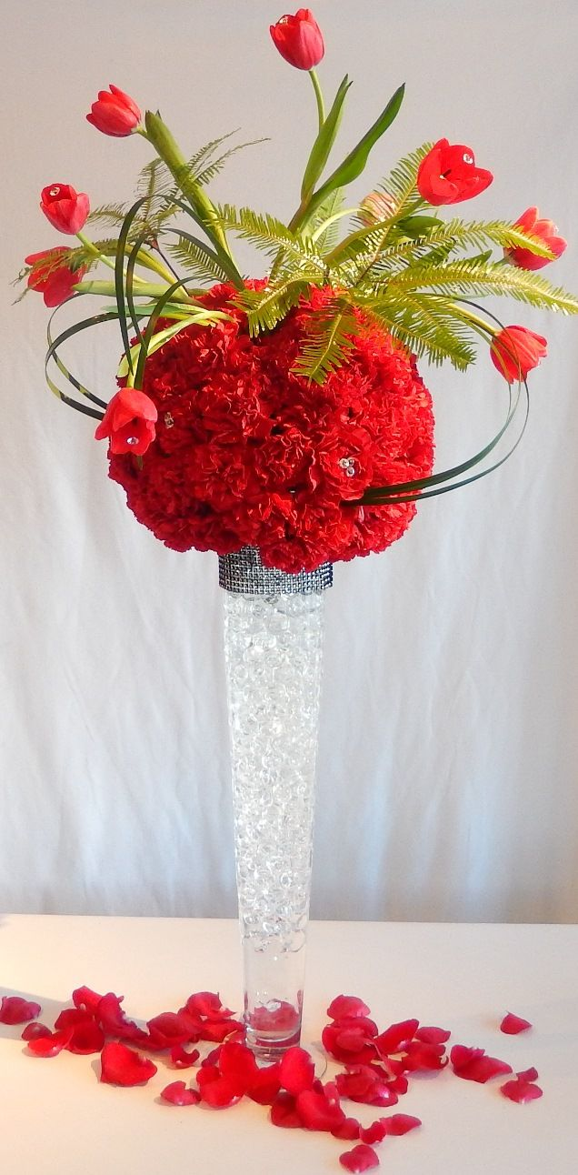 Springtime in Paris centre piece for next weekend's wedding created by Dizennio Floral Boutique-Vaughan. A base of red carnations in a ball form with red tulips studded with crystal pins and strands of lily grass.