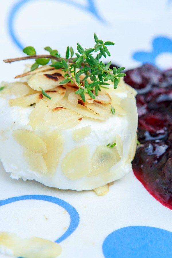 Leckeres Dessert vom Grill, bei dem der Ziegenkäse in Ahornsirup getaucht, mit Mandeln überzogen und dann gegrillt mit Heidelbeer-Ragout serviert wird.
