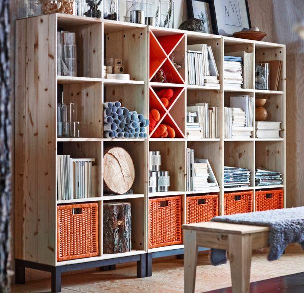 NORNÄS Bücherregale in Kiefer/Grau mit orangefarbenen Körben und Flaschenregalen gefüllt. Davor steht eine NORNÄS Bank in Kiefer.