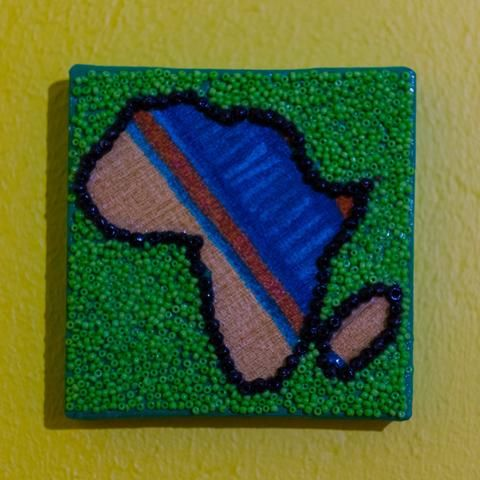 Shop: Canvas D'Afrique - Green Blue. This Africa is partially beaded on canvas in green and black with a center of fabric collage. Size: 10cm x 10cm. By Beadoir D'Afrique