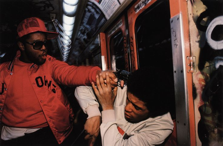 """Bruce Davidson. """"Subway: Undercover Police Officer in Red Jacket, with Gun - In the spring of 1985, New York magazine asked me to photograph a new police-decoy unit working in the subway. Using disguises, the decoy operates in small teams to foil..."""