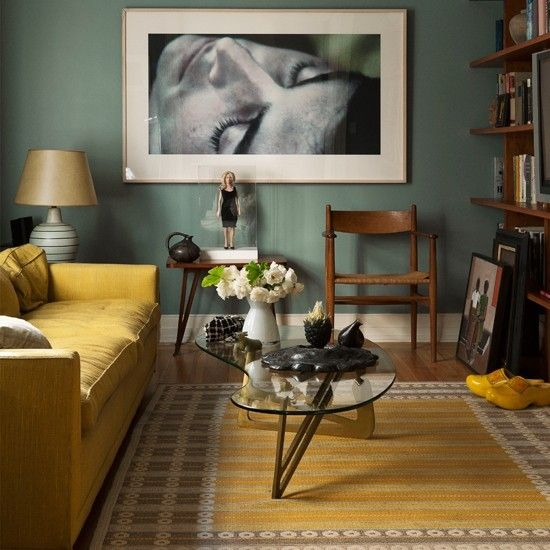Yellow and teal living room    Teal walls combine beautifully with a mustard sofa and rug for a warm scheme. Teak furniture adds a retro feel, while the large black and white framed print completes the look.
