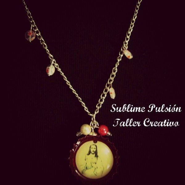 Collar: Sagrado Corazón de Jesús  Materiales: Papel de revista, tapa de gaseosa, resina, cuentas de vidrio, cadena metálica y perlas  Valor: $15.000