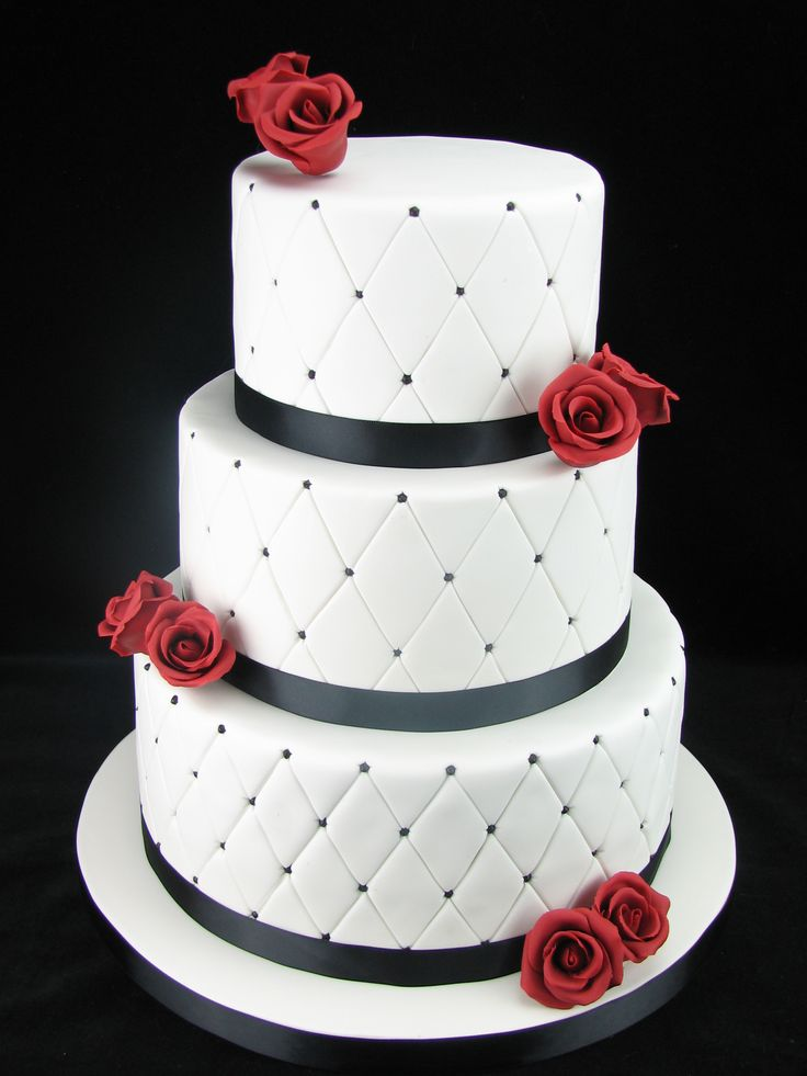 A quilted style tiered wedding cake in classy black and white with burgundy sugar roses. The top tier is red velvet with buttercream. The middle tier is vanilla cake with strawberry jam and buttercream. The bottom tier is chocolate mud cake with dark chocolate ganache. Check out my page at www.facebook.com/cakesbyleannerhodes