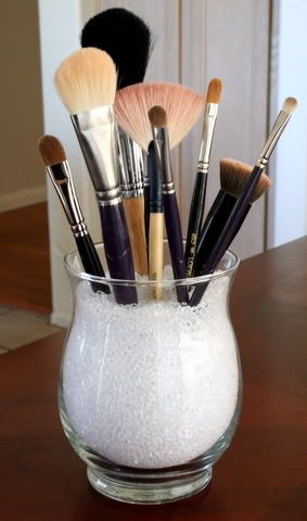 DIY makeup brush holder. a vase, some marbles/rock pieces... bam. easy peas.