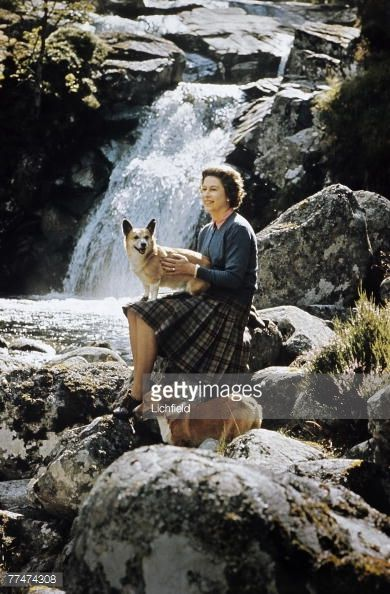HM The Queen sitting on rocks beside a waterfall on the Garbh Allt burn with two corgis on the Estate at Balmoral Castle, Scotland during the Royal Family's annual summer holiday in September 1971....