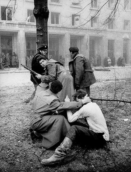Számomra lenyűgözően sokat mond ez a kép: 1956. október 30: a Köztársaság téri pártház ostroma, ahogy védelmezi az egyik megsérült forradalmárt a társa, ahogy visszatekint a másik segítségért, ahogy mindannyian fedezéket keresnek a lövöldöző ávósok golyói elől a fa mögött, ahogy a nézelődők pedig az épület lábazatánál. (Ezen a napon több egészségügyi dolgozó halt meg, mint bármelyik másik napon a forradalom alatt.) Mario De Biasi olasz fotós képe.