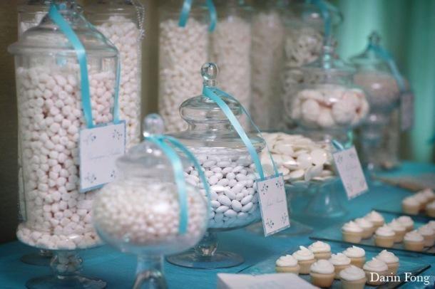 Un centre de table bleu avec perles en verre transparentes, fleurs immergées dans l'eau et lumiere bleue pour centre de table (qui se plonge dans l'eau) Petit vase carré avec bouquet de fleurs bleuet blanc.