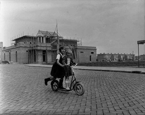 2 meisjes op een autoped in een nieuwbouwwijk in West, Burgemeester Eliasstraat met op de achtergrond de R.K. St. Catharinakerk 'De Lelie' in aanbouw, mei 1956  Foto: Ben van Meerendonk