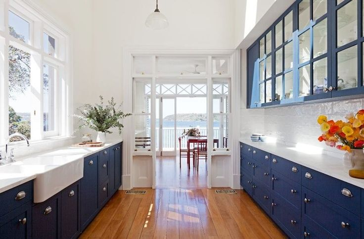 Cobalt blue glass-front kitchen cabinets, marble countertops, white glass subway tiles backsplash, farmhouse sink and lots and