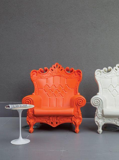 Sillones individuales en naranja y blanco con pequeña mesa haciendo juego. Piso de cerámica y paredes pintadas de gris completan este rincón especial del hotel Nhow Milano.