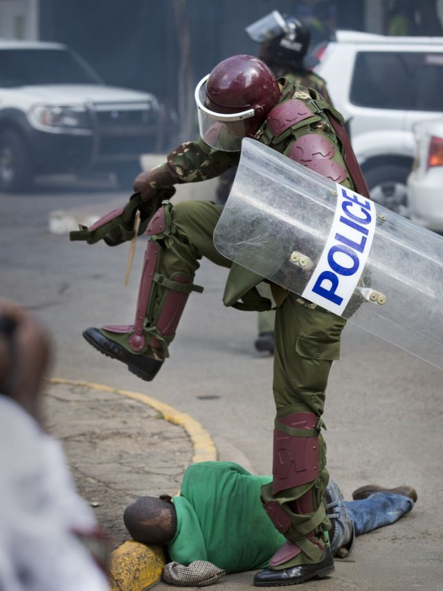 A Kenyan riot policeman repeatedly kicks a protester as he lies in the street. Photography by Ben Curtis