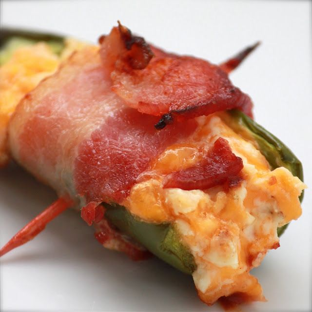 Cheesy BBQ Bacon Jalapenos 20 fresh jalapenos 16 oz. cream cheese (2 packages), room temperature 1 cup shredded cheddar cheese 1/4 teaspoon cumin 1/2 teaspoon paprika 1 lb. bacon, cut into thirds BBQ sauce (Stubbs, if you're especially cool) 40 toothpicks