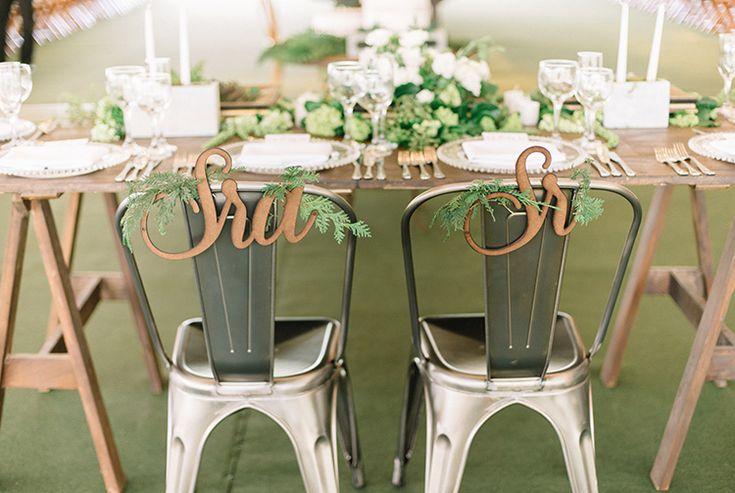 Cadeiras industriais marcando o lugar dos noivos com plaquinhas de MDF recortadas a laser.