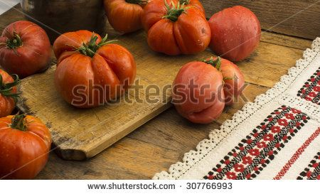 Freshly pick tomatoes, place on wooden chopping board and table.