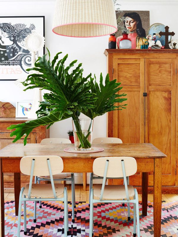 Dining room including chairs by Industria X, Bjørn Wiinblad screenprint, Miss Wong print by Tretchikoff, Victorian farm table belonged to Madeleine's grandparents, and larger than life Monstera leaves from Karl's mother's garden. Photo – Sean Fennessy. Production – Lucy Feagins / The Design Files.