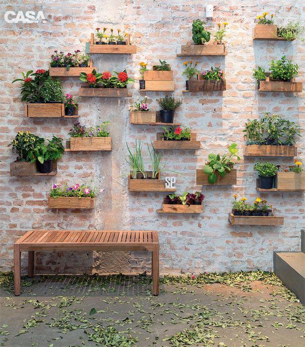 Inspiração do dia: floreiras decoram essa parede de tijolinho.