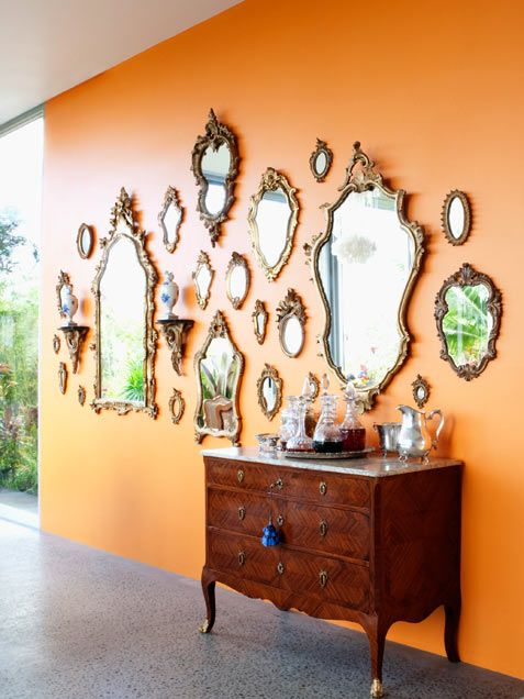 antique mirror collection over an orange wall