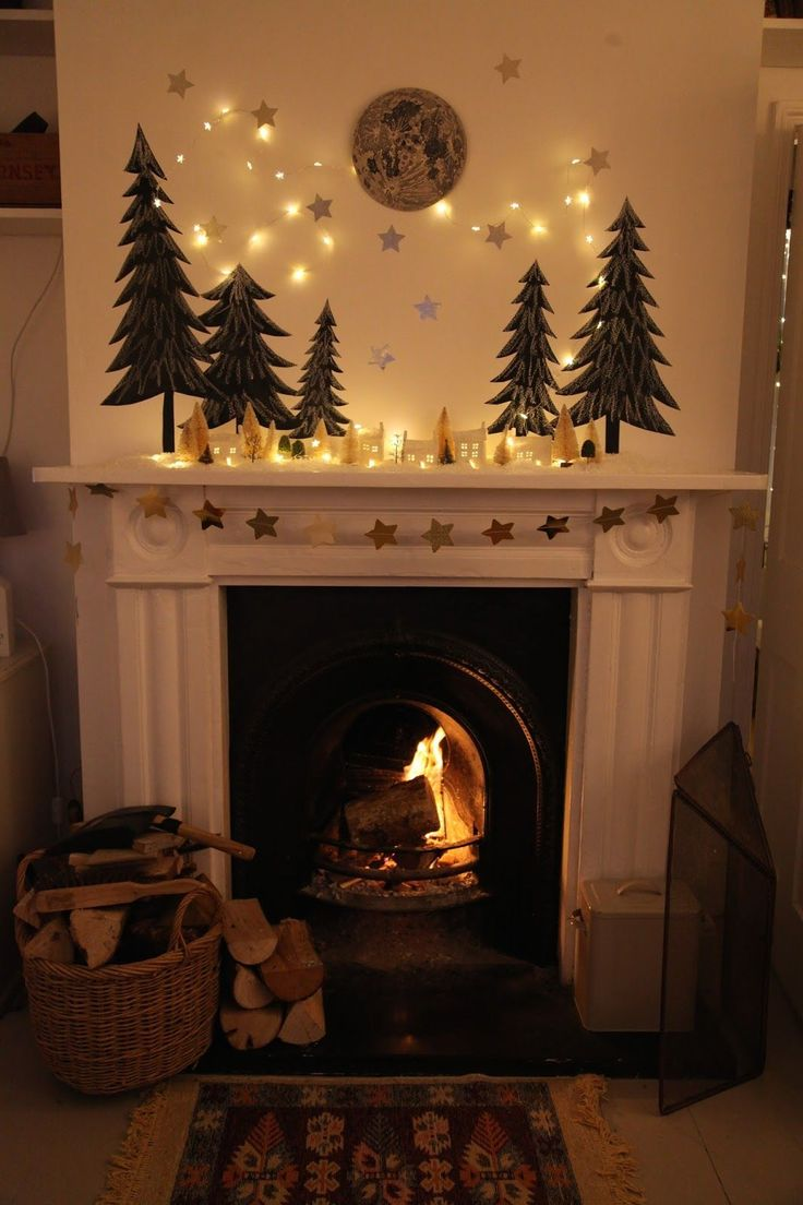 hearth mantel: evergreen trees, moon, ceramic house lanterns, string lights, garland, ...