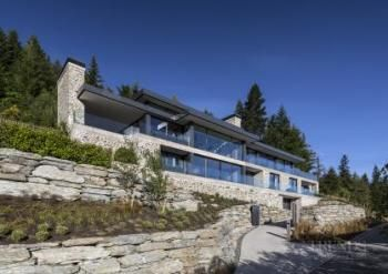 Large house on difficult steep slope is partly dug into the hillside to create a basement platform for the upper levels