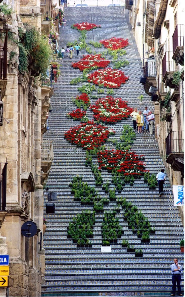 """This """"street art,"""" as Sicilians call it, is very common in Sicily. This is so beautiful and makes a place unforgettable. These are flowers on top of very beautiful steps so they make a very unique design. As you can see, people can walk on these steps and get a closer look at this magnificent artwork."""
