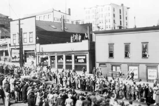 Photograph shows Eighth Street at Columbia Street lined with crowds watching the car carrying King George VI and Queen Elizabeth during their 1939 visit. Businesses shown are Ziegler's Confectioner, the Russell Hotel, and the Premier Hotel.  IHP0892-35